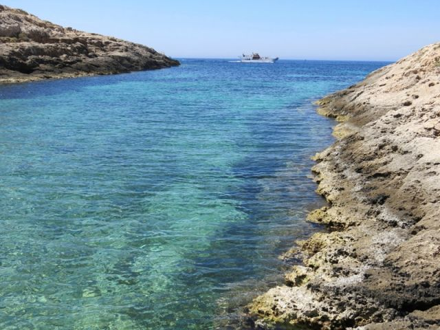 Mare e coste, sullo sfondo una nave a Lampedusa in Sicilia - Movingitalia.it
