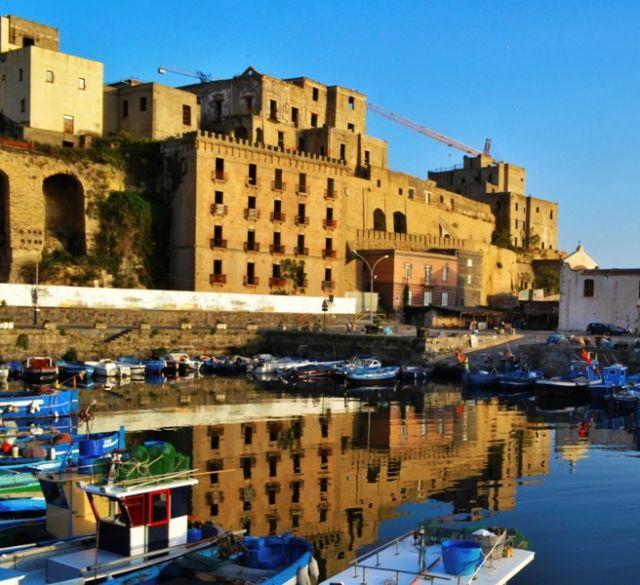 sito archeologico riflesso nel porticciolo della Darsena di Pozzuoli a Napoli - Movingitalia.it