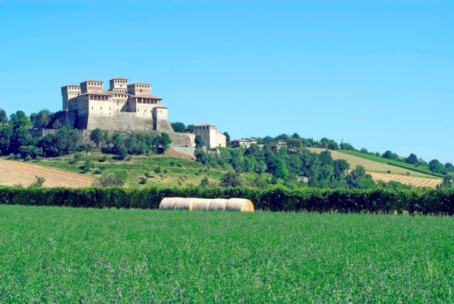 L'esterno del castello di Torrechiara vigneto e prato in una mattina d'estate brillante sotto un cielo blu a Parma