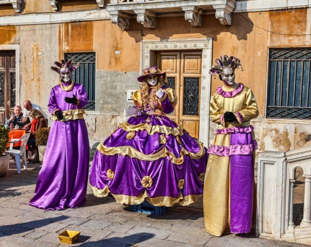 gruppo di tre persone in costume viola e maschere a Venezia durante i giorni del Carnevale - Movingitalia.it