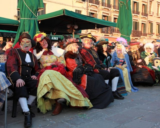 Immagine di un gruppo di turisti travestiti seduti su una terrazza nel sestiere Castello a Venezia, durante i giorni del Carnevale - Movingitalia.it