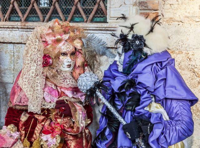 travestiti in costumi specifici in posa vicino a Palazzo Ducale durante i giorni del Carnevale di Venezia. - Movingitalia.it