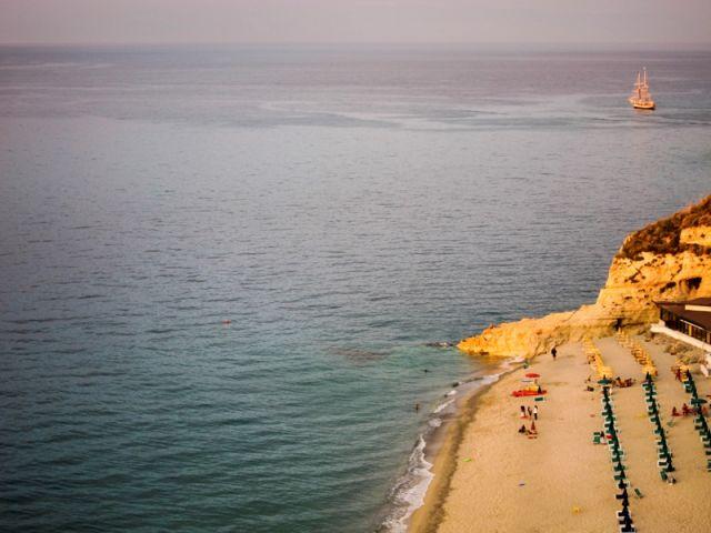 Foto panoramica della spiaggia e mare e sullo sfondo una barca a vela a Tropea in Calabria